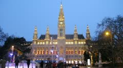 People go for drive on skating rink in front of Rathaus in evening Stock Footage