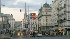 Cars go across evening Vienna towards building of State Opera and Stefansdom Stock Footage