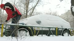 Man in red jacket cleans car from snow Stock Footage