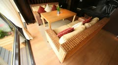 Wicker sofa stand in restaurant lounge fenced  from of terrace by glass door Stock Footage