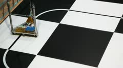 Robot toy car moves along line drawn on large chessboard Stock Footage