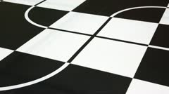 Two robot toy cars moves along intersecting lines drawn on chessboard Stock Footage