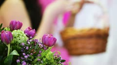 Bouquet flowers in back and defocus girl holding basket of twigs Stock Footage
