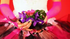 Hands of bride in trendy wedding dress holding bouquet with purple iris Stock Footage