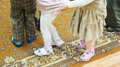 feet of kids walking in circle each other at kindergarten - stock footage