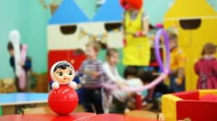 Roly-poly toy on table, then focus moved to children playing with clown Stock Footage