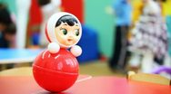 Stock Video Footage of roly-poly toy wobbles on table, in defocus behind it children play