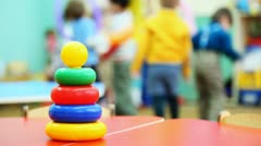 Toy pyramid of colored rings stands on table, in defocus behind it children play Stock Footage