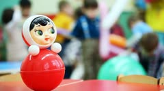 Roly-poly toy on table, then panorama and focus moved to children playing Stock Footage