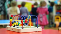 Close-up conundrum toy standing on table, in defocus behind it children play Stock Footage