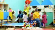 Stock Video Footage of conundrum toy standing on table, in defocus clown blow bubbles for children