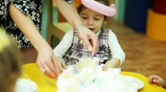 Child-minder lays out pieces of cake to kids sitting at table in kindergarten Stock Footage