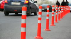 Protective barrier made of striped columns, people and cars go road Stock Footage