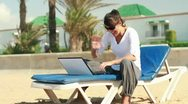 Young happy woman chatting on laptop on the beach Stock Footage