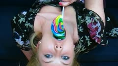 A young woman upside down on the couch licking lollipop Stock Footage