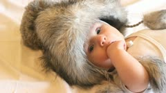Funny baby wearing a big fur hat Stock Footage