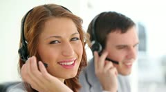 Call centre agents wearing headsets - stock footage