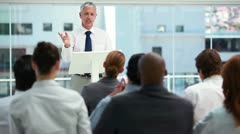Man with grey hair behind a lectern Stock Footage