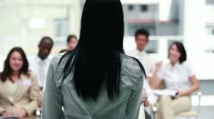 Brunette business woman speaking to business people Stock Footage