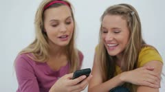 Laughing friends text messaging Stock Footage