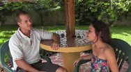 CZA-0040 COUPLE CHATS AT A TABLE Stock Footage