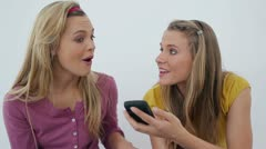 Woman receiving a call while sitting with a friend Stock Footage