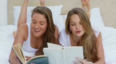 Friends reading books while listening to music together Stock Footage