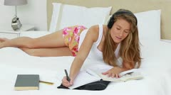 Young brunette woman studying while listening to music - stock footage