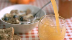 Glass of orange juice in super slow motion being filled Stock Footage