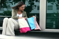 Happy woman with shopping bags sitting by shop window NTSC Stock Footage