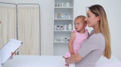 Woman with her baby consulting a general practitioner - stock footage