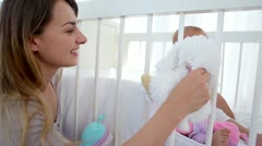Mother giving a cuddly toy to her baby Stock Footage