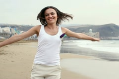 Happy woman running and turning around on beach, slow motion, steadicam shot Stock Footage