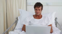 Patient using a laptop while sitting in a sickbed Stock Footage