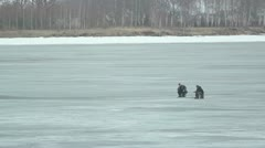 Underwater fishers on frozen lake Stock Footage