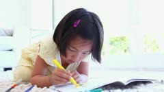 Stock Video Footage of Girl using a marker to colour in a colouring book