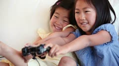 Two sisters playing a games console against each other Stock Footage
