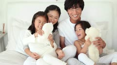 Parents playing with their daughter and teddy bears Stock Footage