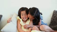 Girl hugging her sister as they sit together Stock Footage
