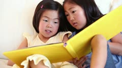 Two girls reading a book together Stock Footage
