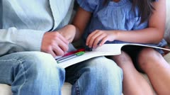 Girl colouring a book on her fathers lap Stock Footage