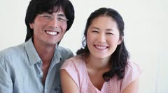 Couple laughing as they sit together - stock footage