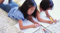 Two girls colouring while lying next to each other Stock Footage