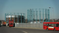 Gas storage holder with red buses Stock Footage