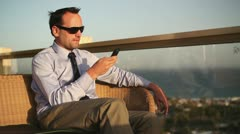 Businessman using smartphone on balcony with beautiful view HD Stock Footage