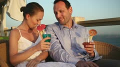 Young couple talking and drinking exotic cocktails on balcony HD Stock Footage