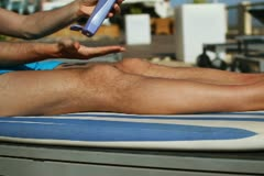 Man applying sun block lotion on leg NTSC Stock Footage