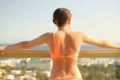 Sexy young woman relaxing on terrace with beautiful view NTSC Stock Footage