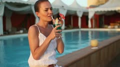 Happy woman drinking exotic cocktail by swimming pool HD Stock Footage