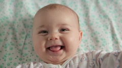 Cute baby lies on back and smiling (closeup) Stock Footage